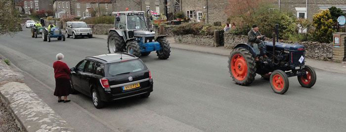 Photo of the vintage tractors going up High Street Cropton - Beadlam Charity Tractor Run 2013